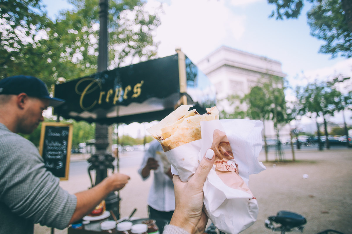 Barefoot Blonde Crepes in front of Arc de Triomphe