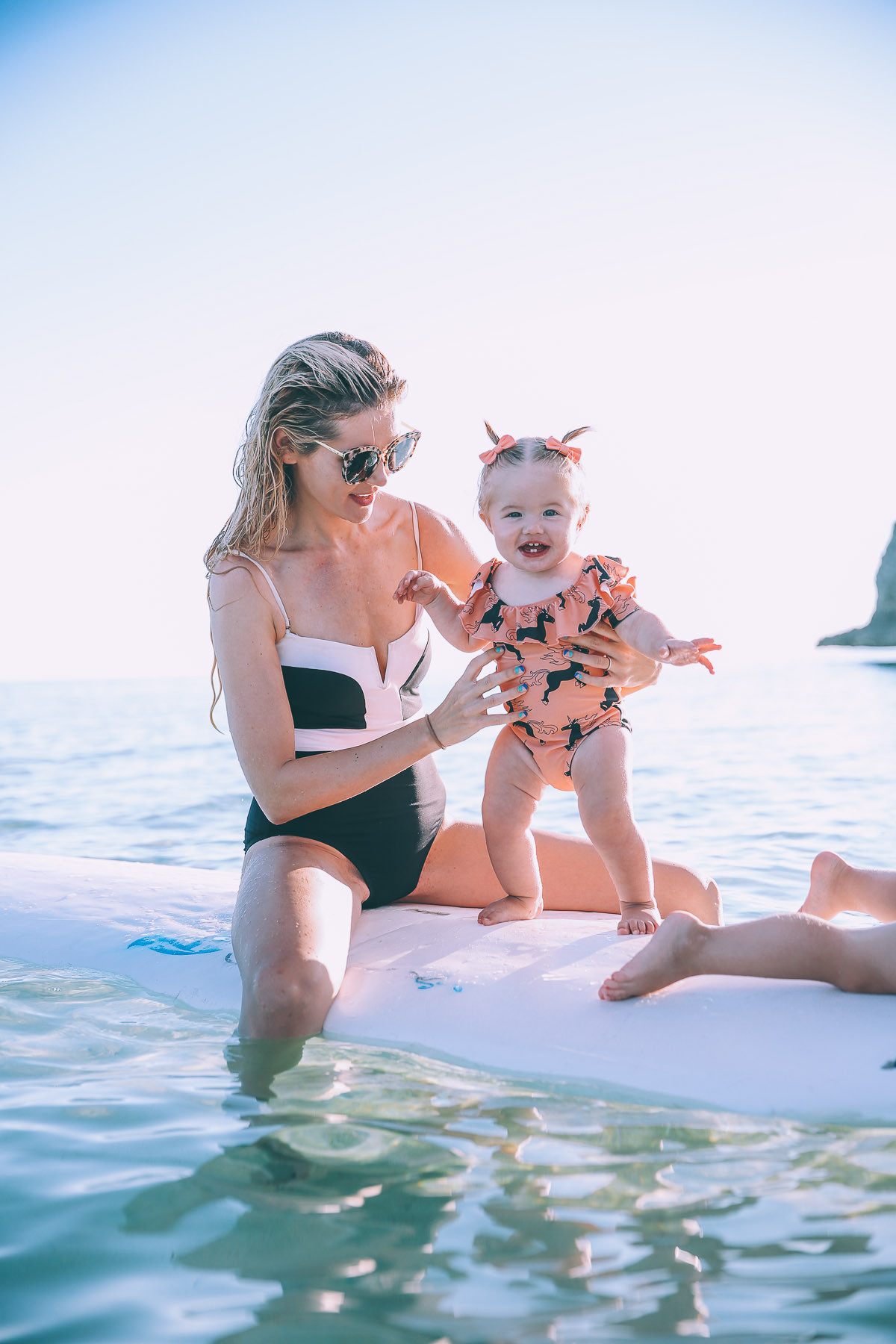 Barefoot Blonde Amber and Rosie standing on Paddle Board in Bahamas