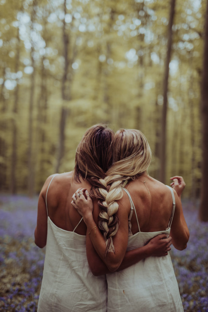 Amber and Tessa in a forest of flowers in Belgium with braids intertwined. Barefoot Blonde / Amber Fillerup Clark