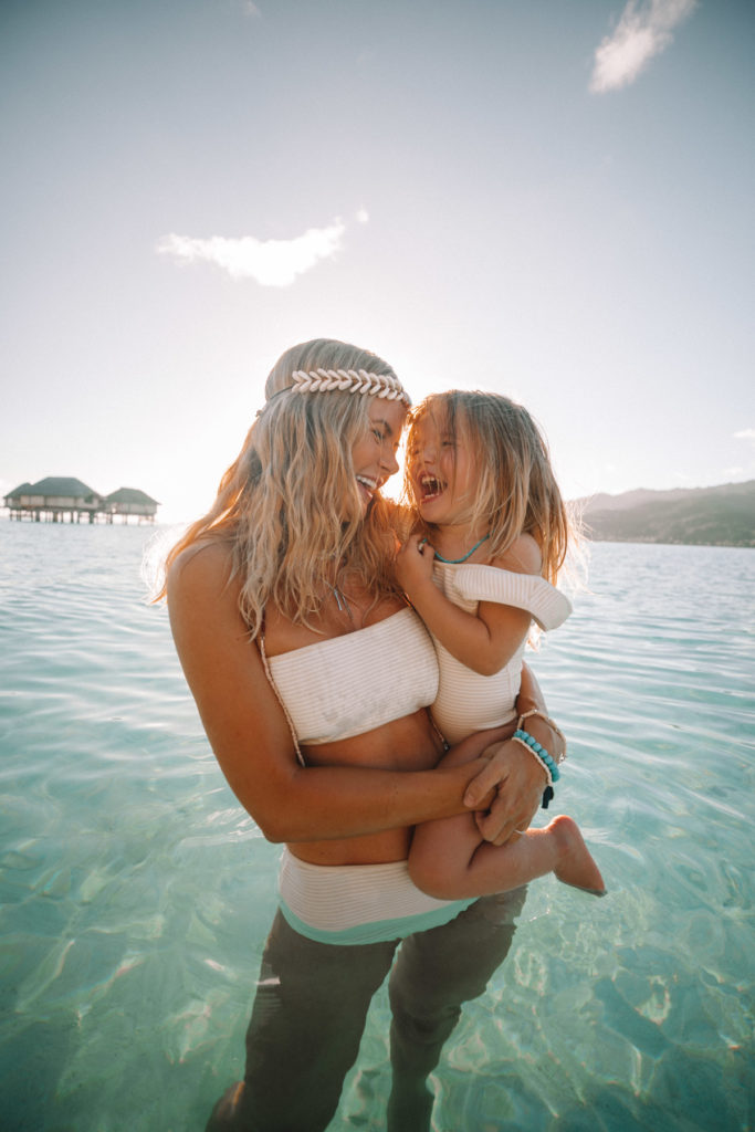 Tahiti Travel Diary image of Amber wearing a gold headband with Rosie in the ocean. Amber Fillerup, Barefoot Blonde