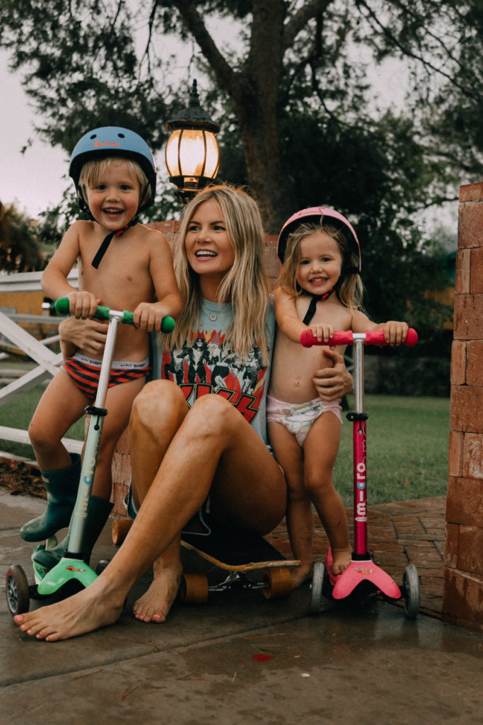 Amber, Rosie and Atticus playing in the rain with their scooters during the kids first haboob in Arizona. Barefoot Blonde / Amber Fillerup Clark