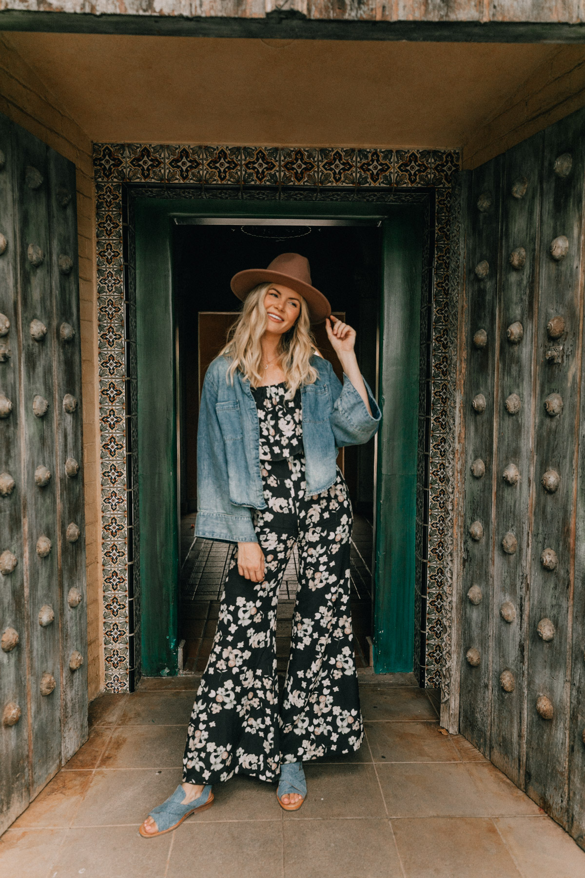 Amber Fillerup wearing a hat, floral black jumpsuit, blue sandals and a denim jacket in Arizona for her post on the top 8 tips for new bloggers. Barefoot Blonde / Amber Fillerup