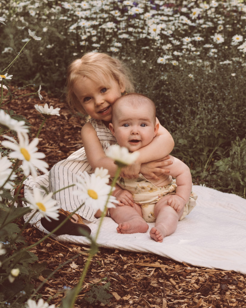 Barefoot Blonde contributor Christina Loewen's daughters in a field of wildflowers for her article on being a patient parent. Barefoot Blonde / Amber FIillerup