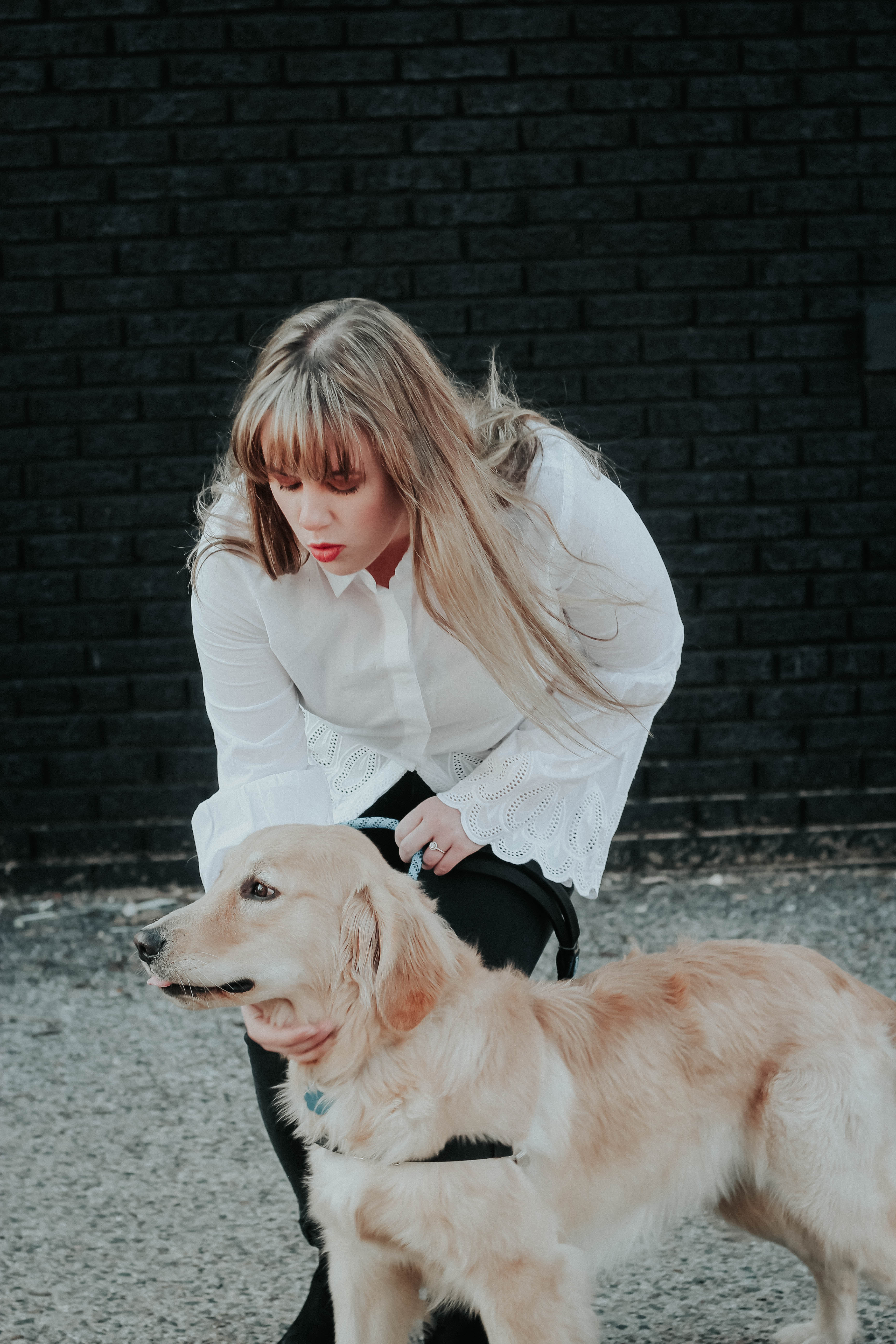 Contributor Kylie Thompson with bangs playing with her dog. Kylie answers the question on what you should consider when getting bangs. Barefoot Blonde.