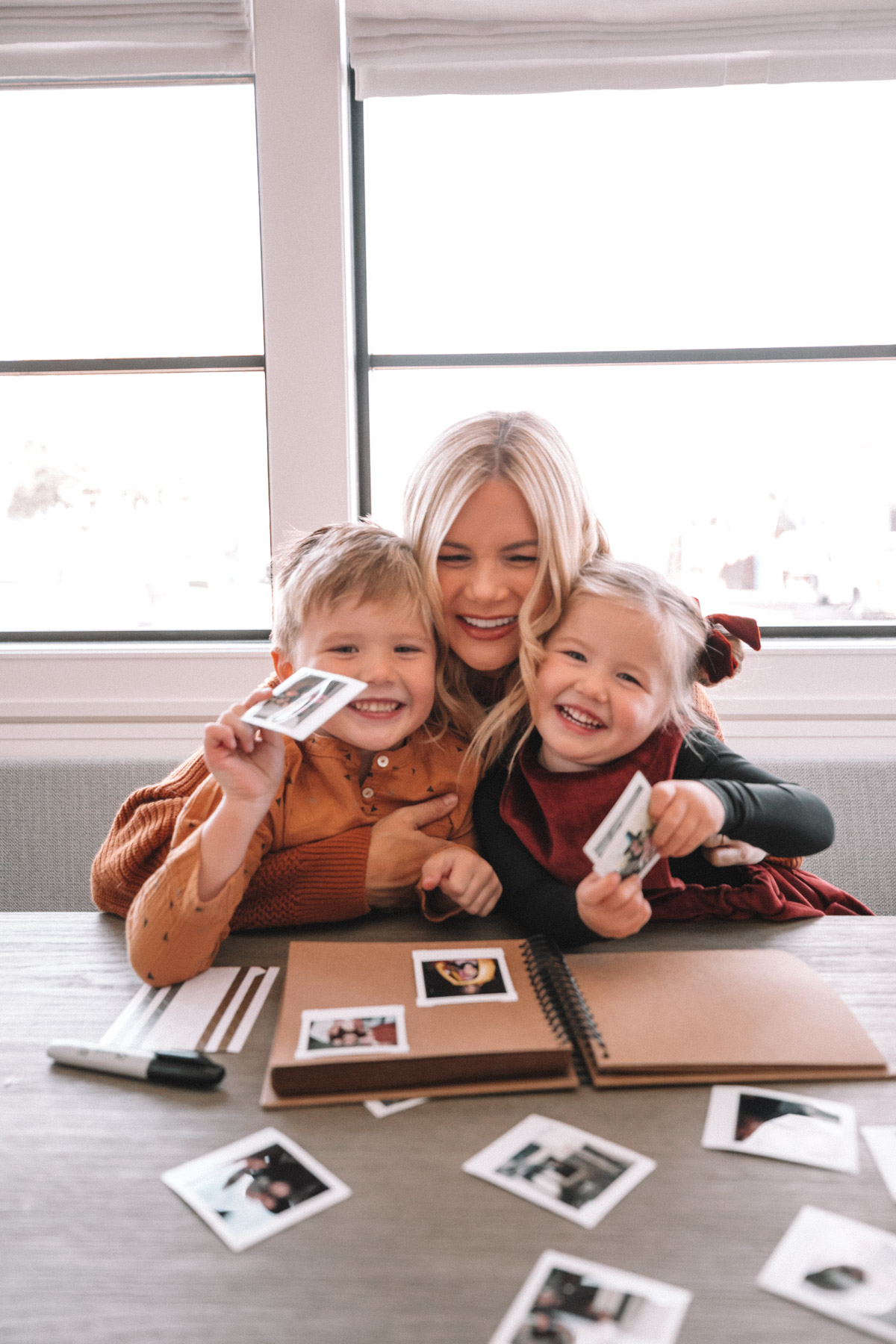 Atticus, Amber and Rosie scrapbooking with their Fujifilm camera prints. A Meaningful Gift for Grandma and Grandpa | Barefoot Blonde | Amber Fillerup Clark