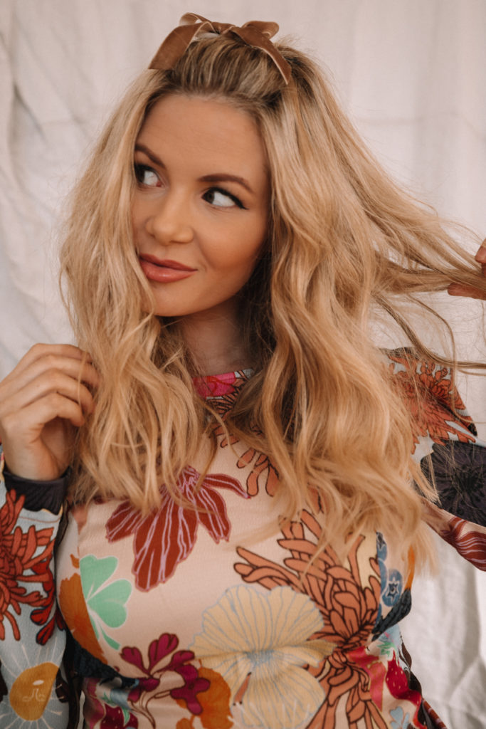 Amber Fillerup Clark of Barefoot Blonde wearing a colorful dress for the blog post on her 6 most recent reads of 2019. Barefoot Blonde