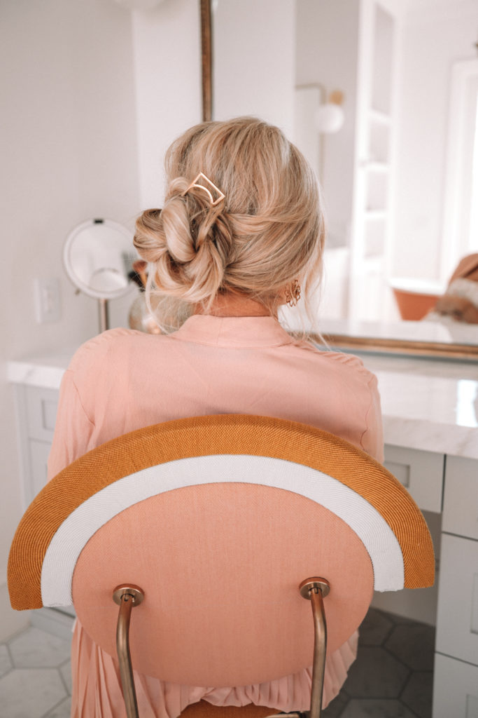 Amber Fillerup Clark in her bathroom in her new home at her vanity showing a formal updo, one of her favorite simple hairstyles.