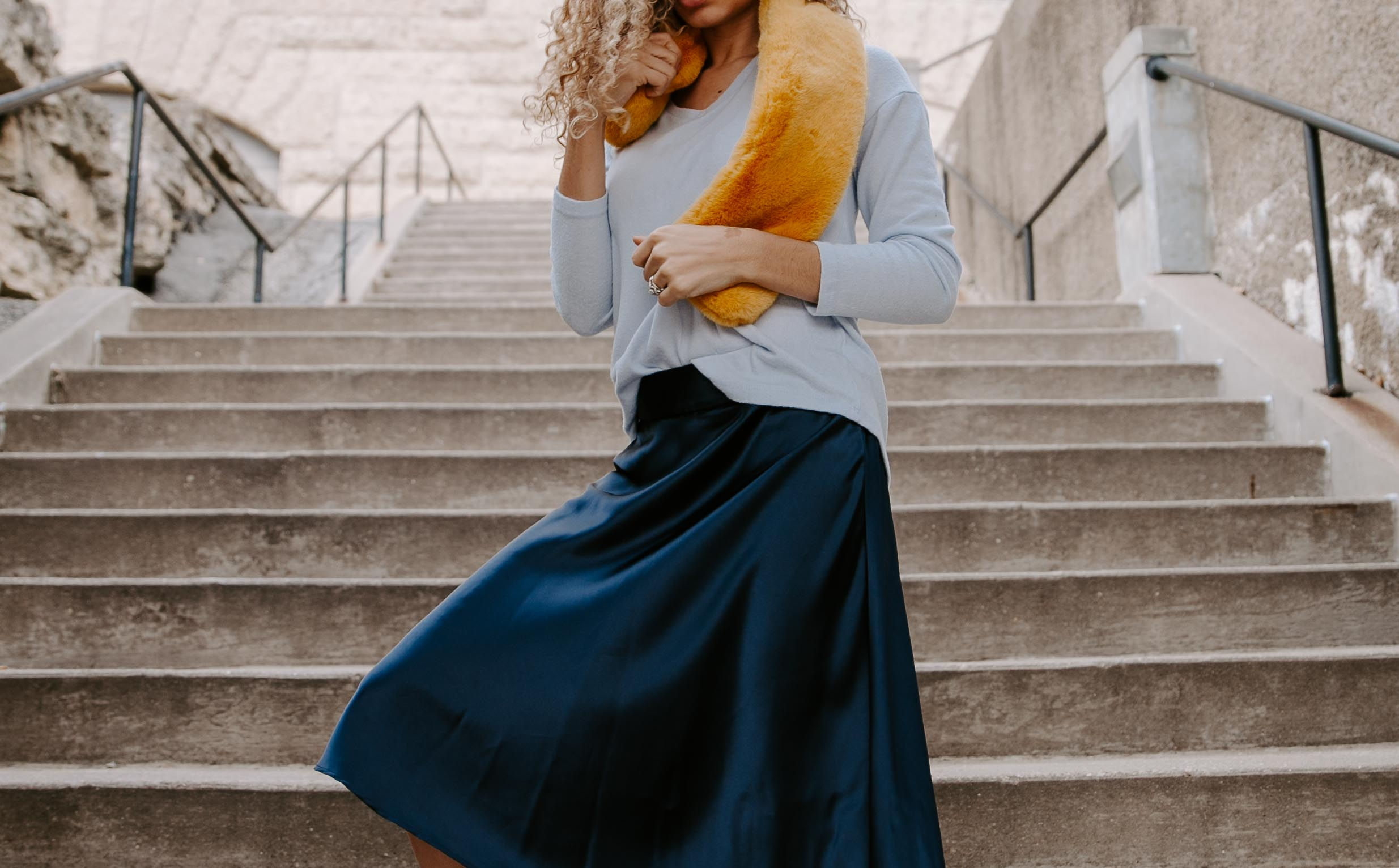 Contributor Carolyn Arentson of My Chic Obsession, wearing a monochromatic outfit of different blue tones. A dark blue skirt and a light blue sweater, styled with a bright yellow fur scarf.