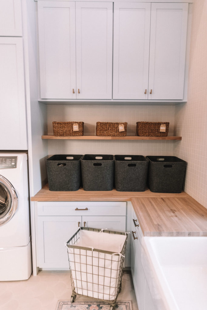 Blue cabinets and bins for organization in Amber Fillerup Clark's brand new Laundry Room. Barefoot Blonde.