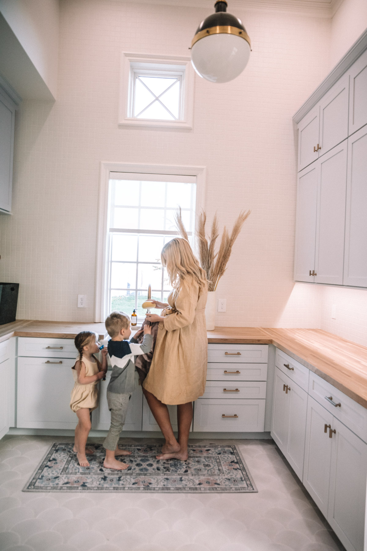 Amber Fillerup Clark with Atticus and Rosie in their laundry room in their brand new home.