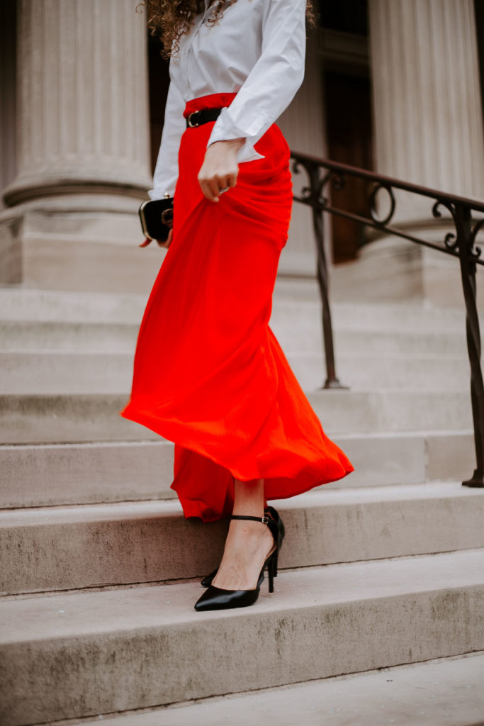 BFB Contributor Carolyn Arentson wearing a bright red maxi skirt with a white blouse and belt. Barefoot Blonde.