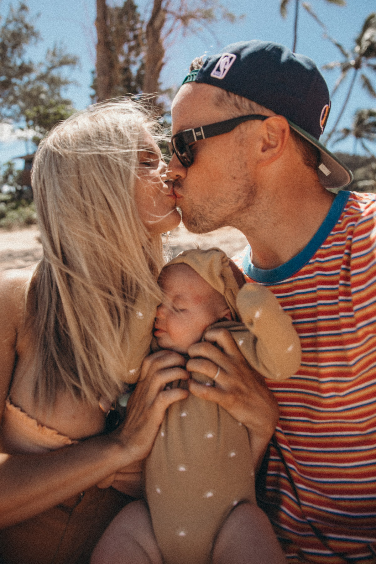 Amber and David kiss while holding Frankie on the beach in Hawaii. Barefoot Blonde | Amber Fillerup Clark